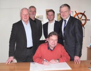 Hans Pawlowski unterzeichnet für den Stadtsportverband den neuen Pakt für den Sport. Rainer Krüger, Karl-Heinz Mense, Philip Pauge und Dr. Reiner Austermann schauen ihm dabei über die Schulter.